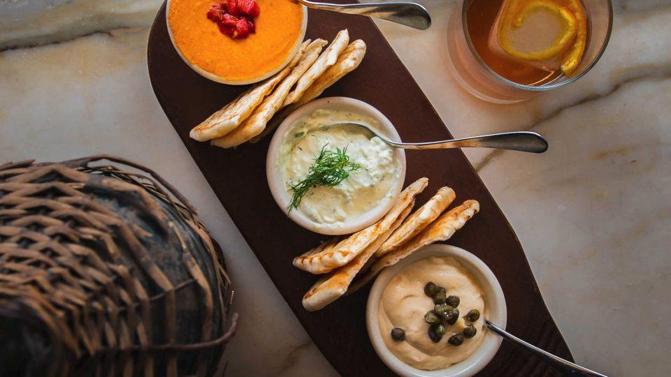 A collection of spreads with pita bread